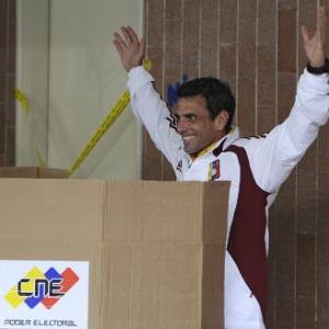 14.abr.2013 - Henrique Capriles, candidato à presidente da Venzuela da oposição, acena para fotógrafos durante preparação para votar em Caracas, capital do país. De acordo com pesquisas, Nicolás Maduro, sucesso de Chávez, tem uma pequena vantagem sobre Capriles - Leo Ramirez/AFP