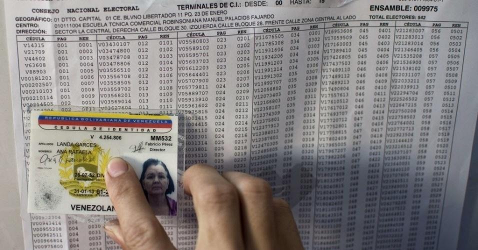 14.abr.2013 - Mulher confere localização de sua seção eleitoral durante votação em Caracas neste domingo (14)