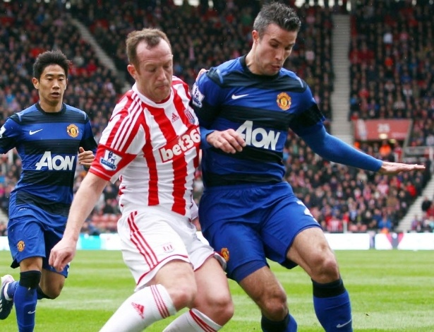 14.abr.2013 - Van Persie (dir.), atacante holandês do Manchester United, disputa a posse da bola com Charlie Adams, do Stoke City, em partida do Campeonato Inglês