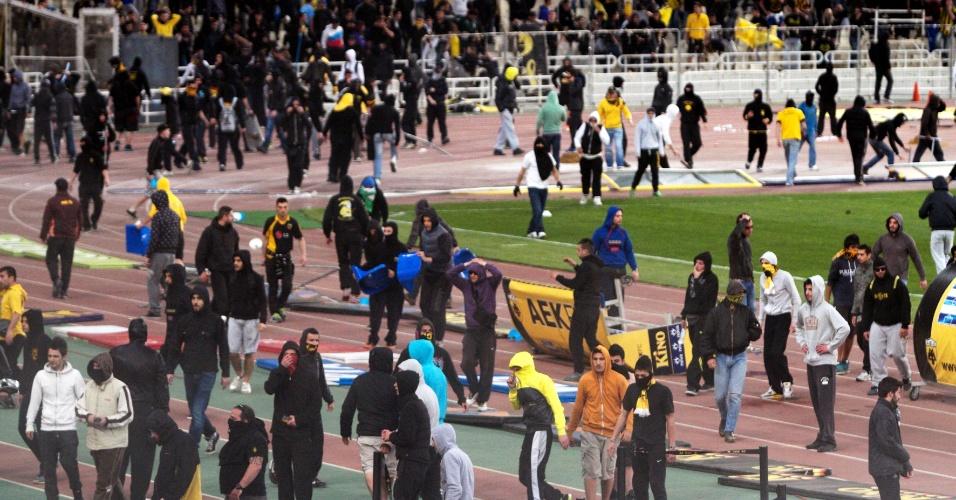 14.abril.2013- Torcedores do AEK invadem campo e perseguem jogadores na Grécia