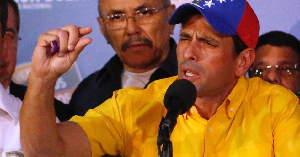 15.abr.2013 - Henrique Capriles, candidato oposicionista derrotado na eleição presidencial da Venezuela, faz gesto para ilustrar a pequena margem de votos que o separou do vencedor, o chavista Nicolás Maduro. Durante o discurso, Capriles anunciou que não aceita a vitória de Maduro e vai pedir a recontagem dos votos
