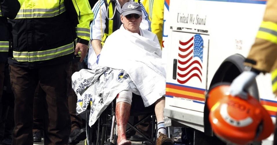 15.abr.2013 - Homem é socorrido e levado para ambulância ao ter a perna ferida em explosões na Maratona de Boston