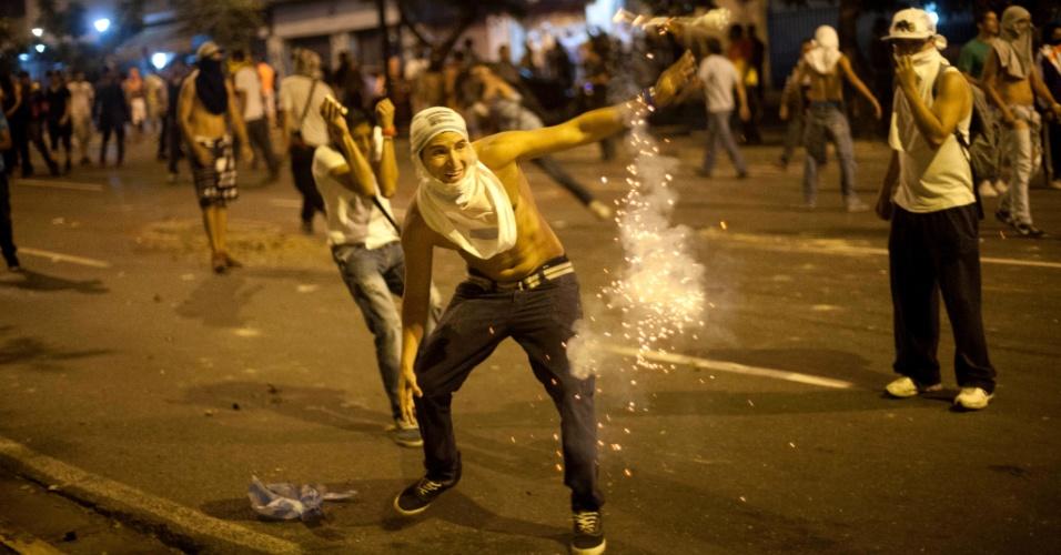 15.abr.2013 - Manifestante joga explosivo em direção à polícia durante protesto contra a eleição de Nicolás Maduro em caracas, capital da Venezuela.foram usadas bombas de gás lacrimogênio para dispersar a multidão
