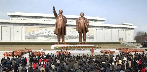 Norte-coreanos depositam flores diante de estátua do fundador do país, Kim Il-sung, durante celebrações do 101º aniversário do nascimento do antigo líder do país - KCN/EFE