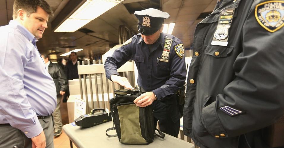 15.abr.2013 - Policiais inspecionam mala de homem no Grand Central Terminal, em Manhattan, Nova York. A cidade anunciou que vai aumentar a fiscalização nos terminais para se prevenir contra ataques terroristas