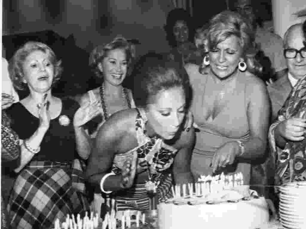 A atriz Ceyde Yáconis (segunda, da esquerda para a direita) bate palmas durante o aniversário de Lolita Rodrigues em 1975. Ao lado, a apresentadora Hebe Camargo - Folhapress