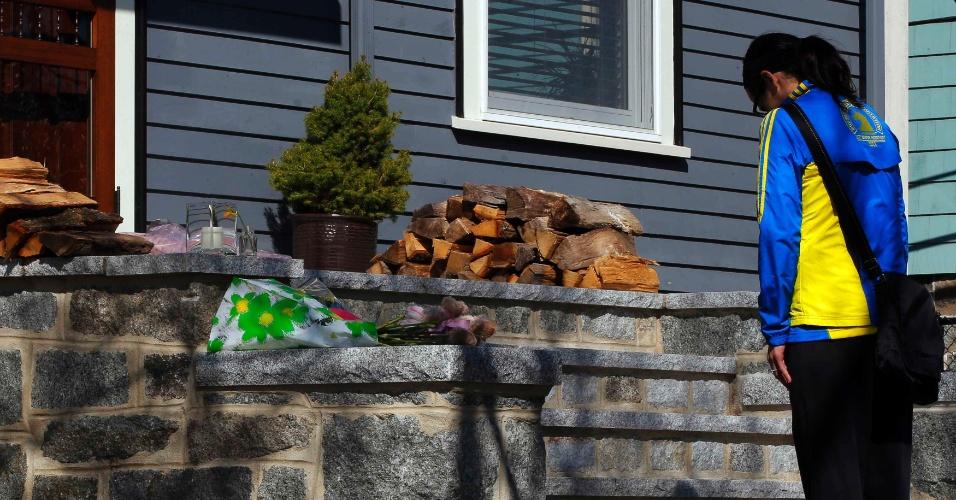 16.abr.2013 - A maratonista Megan Cloke deixa flores na porta de Martin Richard, de oito anos, vítima das explosões na Maratona de Boston, nesta terça-feira (16). Três pessoas morreram nos atentados e 176 ficaram feridas