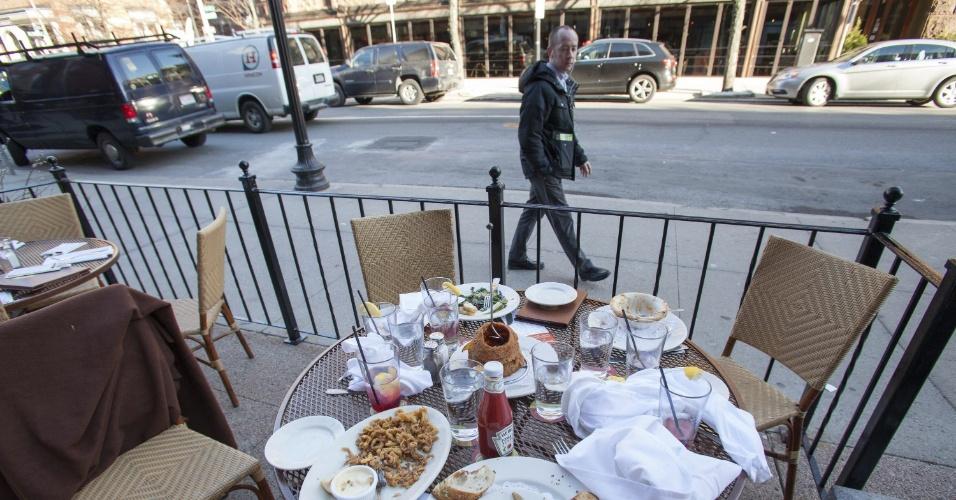 16.abr.2013 - Homem passa em frente a restaurante na rua Newbury, perto do local onde era realizada a Maratona de Boston (EUA), nesta terça-feira (16). Pratos de refeições foram deixados como estavam após a correria que se seguiu às explosões na cidade