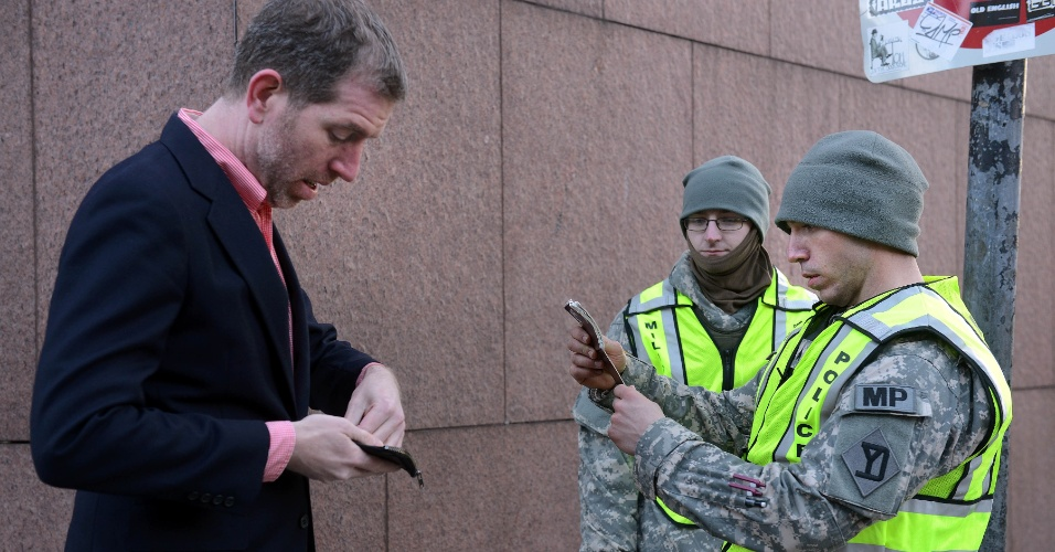 16.abr.2013 - Policial checa documento de identidade de homem na avenida Massachusetts, em Boston, nos EUA, nesta terç-afeira (16). A cidade teve a segurança reforçada após os atentados a bomba que tiveram como alvo a Maratona de Boston