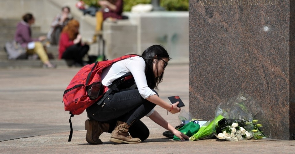 17.abr.2013 - A estudante de jornalismo Joy Liu deixa um boné irlandês e um bilhete em local na Universidade de Boston em memória de Lu Lingzi, chinesa de 23 anos que é uma das vítimas dos atentados que mataram três pessoas durante a Maratona de Boston (EUA). Lingzi era estudante de estatística