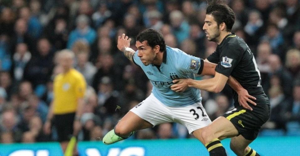 17.abr.2013 - Carlos Tevez, meia argentino do Manchester City, disputa a bola com Jordi Gomez, do Wigan, em jogo do Campeonato Inglês