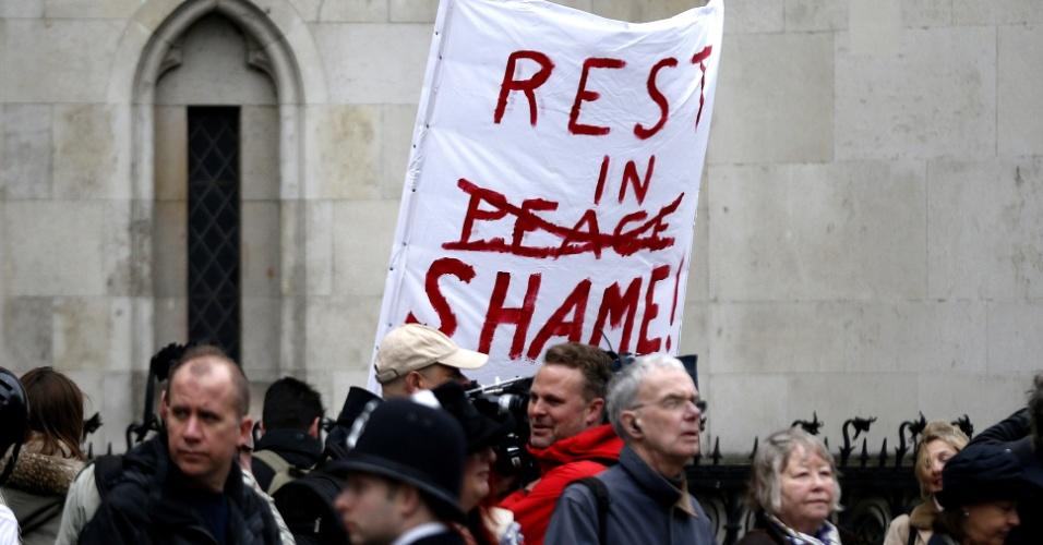 17.abr.2013 - Cartaz de protesto é erguido entre pessoas que se reúnem em rota de procissão do funeral da ex-primeira-ministra britânica Margaret Thatcher. Em evento raro, a rainha Elizabeth 2ª comparecerá ao funeral da controversa política. No cartaz, lê-se em inglês, fazendo um trocadilho: