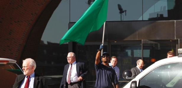 Homem segura uma bandeira verde, sinalizando que é seguro retornar ao prédio do tribunal de Boston - Jessica Rinaldi/Reuters