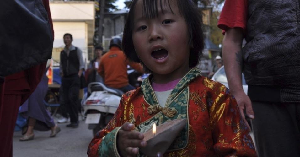 17.abr.2013 - Menina tibetana segura vela acesa durante encontro de tibetanos exilados em Dharamsala, na Índia