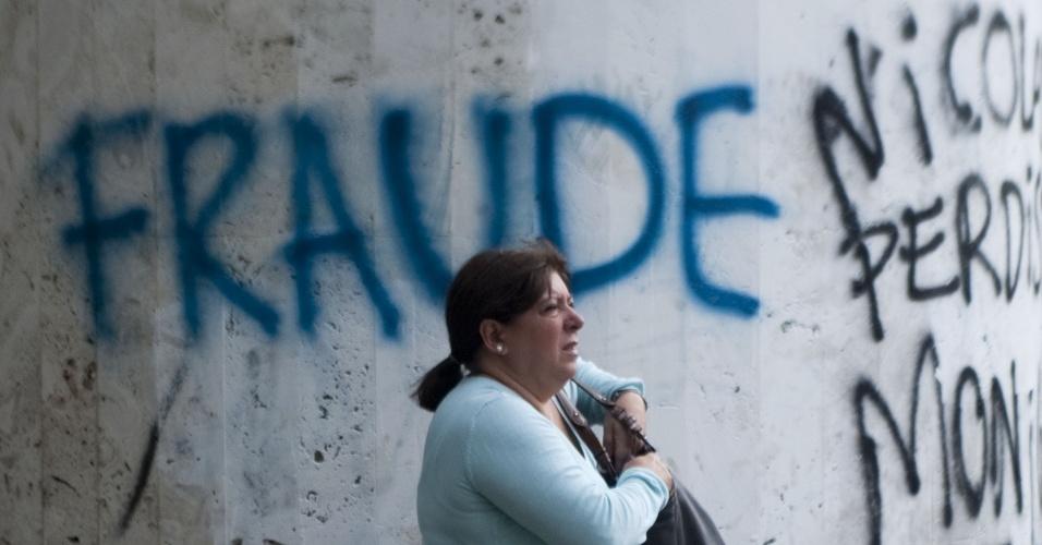 """17.abr.2013 - Mensagens pichadas nos muros de Caracas afirmam """"fraude"""" nas eleições venezuelanas e dizem que a ascensão de Nicolás Maduro à presidência do país é ilegítima. Nas eleições realizadas no último domingo (14), após a morte do ex-presidente Hugo Chávez, Maduro, indicado por Chávez para sucedê-lo, bateu o líder oposicionista Henrique Capriles pela diferença apertada de 1,7% de votos"""