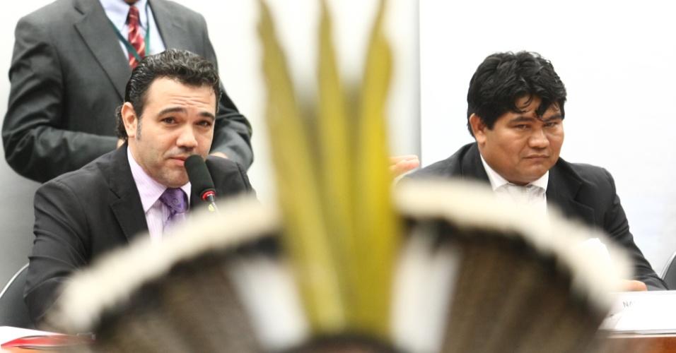 17.abr.2013 - O presidente da Comisso de Direitos Humanos da Câmara, deputado Marco Feliciano (sentado, à esq.), é visto atrás de um cocar de uma liderança indígena que participou da sessão da comissão nesta quarta-feira (17)