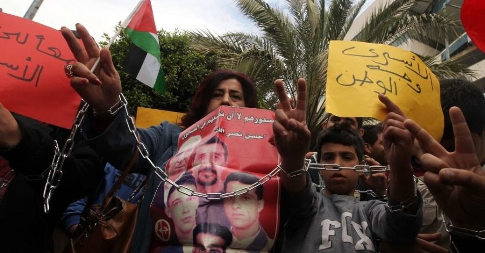 17.abr.2013 - Palestinos protestam com bandeiras e fotografias de seus familiares presos em cárceres israelenses, pedindo a libertação dos mesmos, no Dia do Prisioneiro, em Nablus, na Cisjordânia. Há cerca de 5.000 palestinos em centros de detenção israelenses