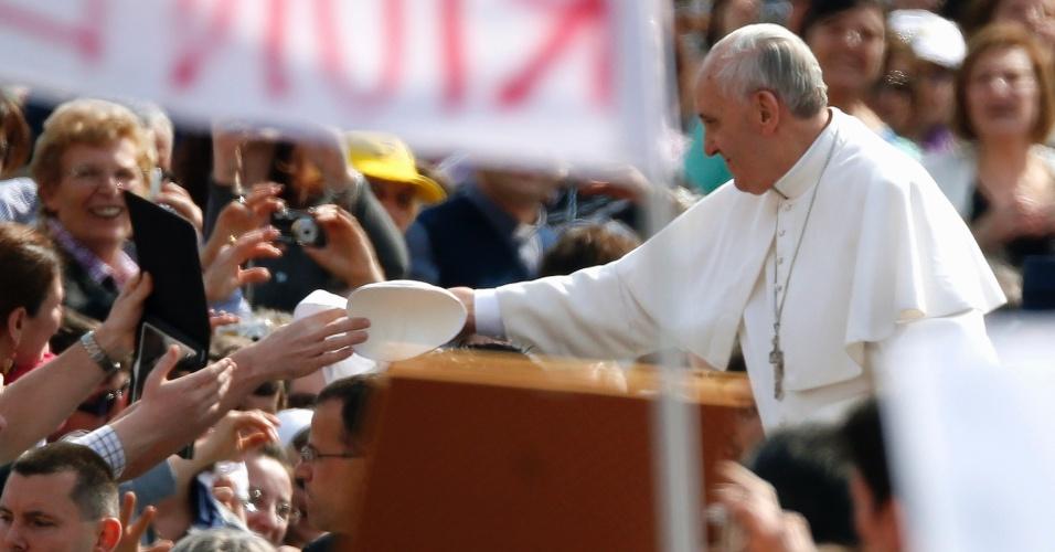 17.abr.2013 - Papa Francisco troca de solidéu, o tradicional chapéu papal, com um fiel na praça de São Pedro, no Vaticano, durante audiência geral