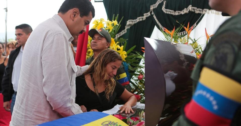 17.abr.2013 - Presidente eleito da Venezuela Nicolás Maduro conforta a viúva Jose Luis Ponce, eleitor que morreu durante os confrontos que sucederam ao anúncio da vitória do candidato governista. O funeral foi realizado no bairro de La Limonera, no Estado de Miranda, no norte da Venezuela