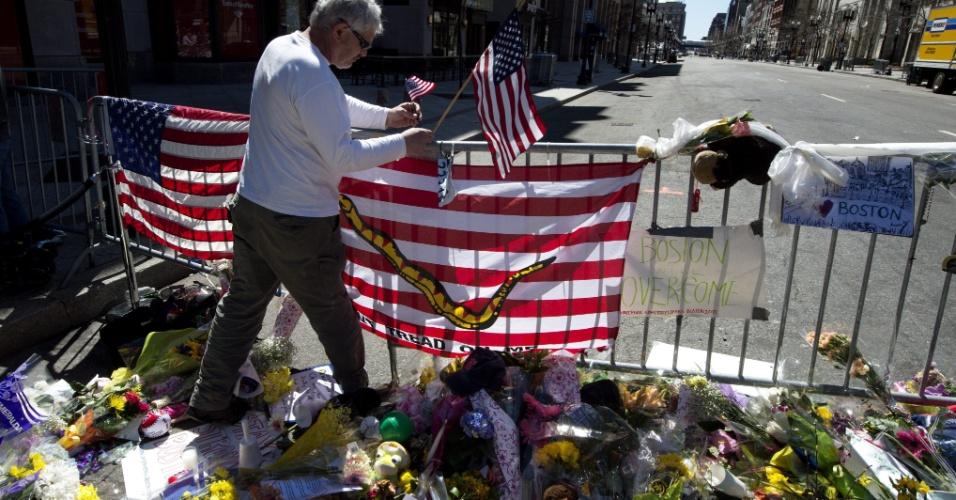 17.abr.2013 - Homem coloca bandeira dos Estados Unidos em memorial em homenagem às vítimas das explosões na Boylston Street, durante a Maratona de Boston, ocorridas na segunda-feira (15)