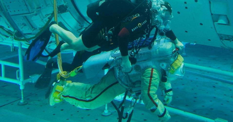 18.abr.2013 - Alexander Gerst, da Agência Espacial Europeia, nada com mergulhadores em uma piscina do centro de treinamento de Star City, região de Moscou, na Rússia. O alemão é um dos engenheiros de voo da missão 40 da Estação Espacial Internacional (ISS, na sigla em inglês), prevista para maio de 2014