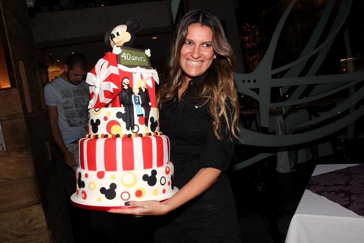 18.abr.2013 - Andréa Guimarães segura o bolo de aniversário de 40 anos de Adriane Galisteu em restaurante em SP