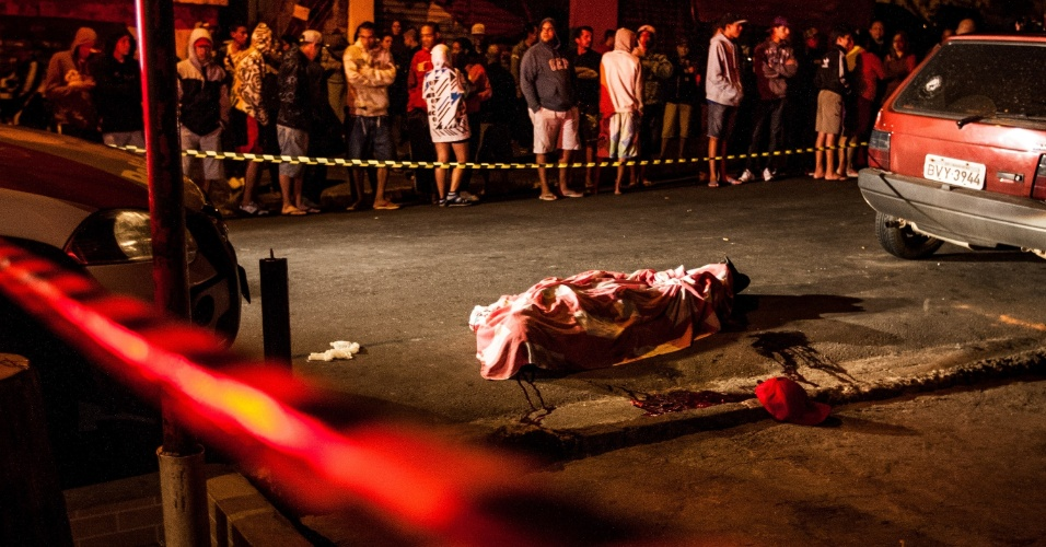 18.abr.2013 - Corpo de homem morto a tiros na porta de um bar na avenida Jupiter, em Carapicuiba, na grande Sao Paulo. Quatro pessoas que estavam no local também foram baleadas. Uma segunda vítima morreu no hospital e outras três foram internadas