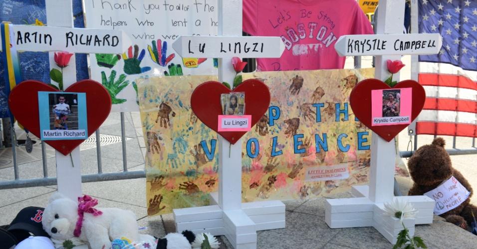 18.abr.2013 - Cruzes com corações contendo o nome das três pessoas que morreram no atentado à Maratona de Boston foram colocadas no memorial improvisado na rua onde ocorreram as explosões, em Boston, Estados Unidos