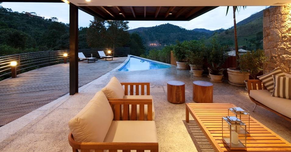 O deck funciona como uma extensão do espaço interno, proporcionando integração entre a piscina e churrasqueira. A piscina triangular tem uma área de 17,45 m². A residência de montanha localizada no bairro Itaipava, em Petrópolis (RJ), é um projeto da arquiteta Flávia Quintanilha