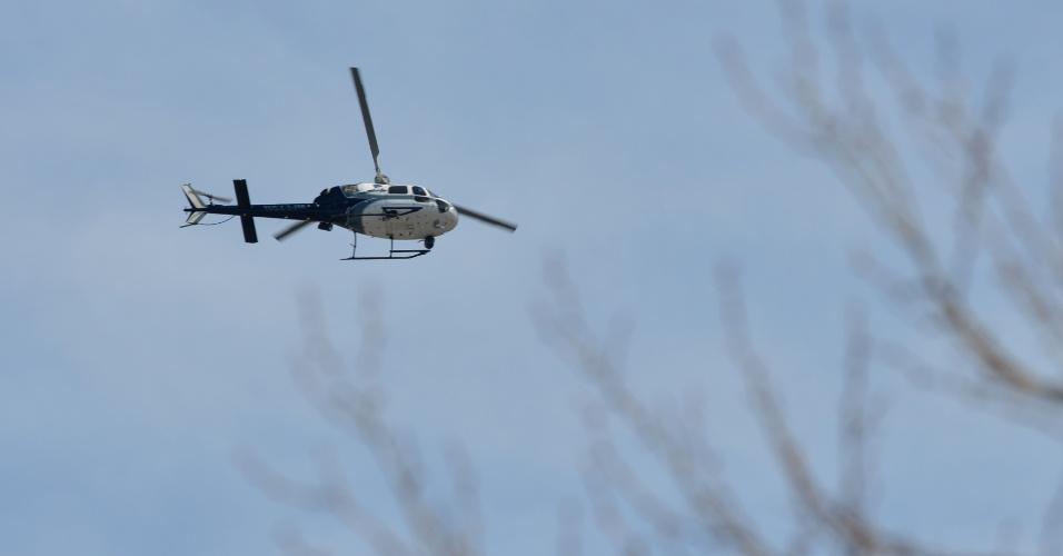 19.abr.2013 - Helicóptero da polícia sobrevoa bairro durante procura por um dos suspeitos dos atentados na Maratona de Boston, em Watertown, Massachusetts, nesta sexta-feira (19)
