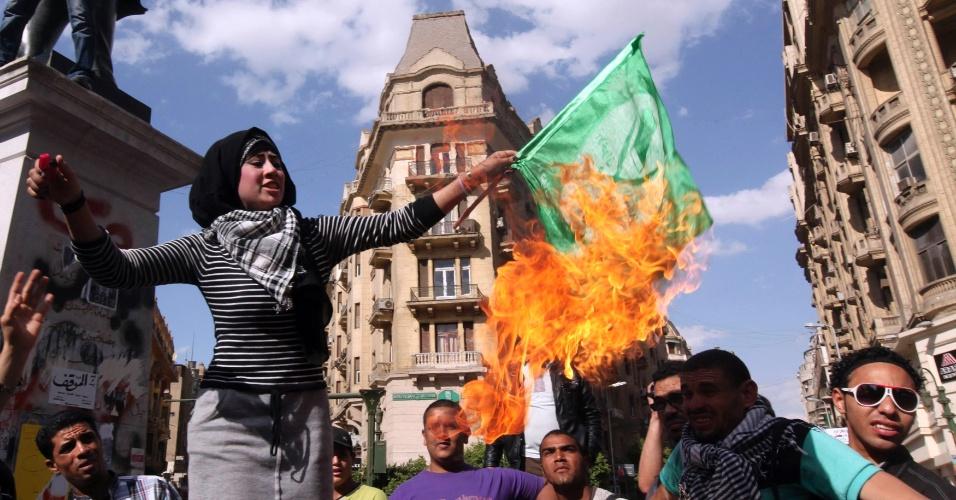 19.abr.2013 - Manifestante antigoverno ateia fogo em bandeira da Irmandade Muçulmana na praça Tahrir, no Cairo, no Egito