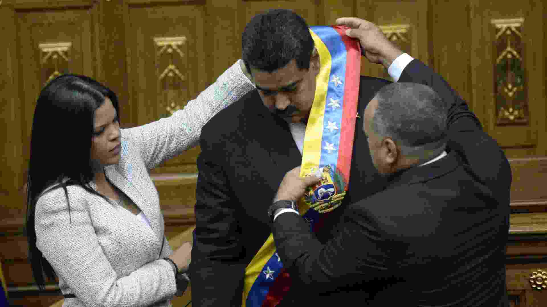 19.abr.2013 - Maria Gabriel Chávez (à esq.), filha de Hugo Chávez, e o presidente da Assembleia Nacional da Venezuela, Diosdado Cabello, colocam a faixa presidencial em Nicolás Maduro, em cerimônia de posse no cargo nesta sexta-feira (19), na sede da Assembleia Nacional, em Caracas - Juan Barreto/AFP
