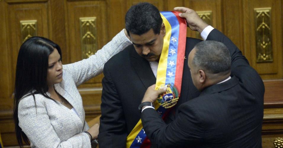 19.abr.2013 - Maria Gabriel Chávez (à esq.), filha de Hugo Chávez, e o presidente da Assembleia Nacional da Venezuela, Diosdado Cabello, colocam a faixa presidencial em Nicolás Maduro, em cerimônia de posse no cargo nesta sexta-feira (19), na sede da Assembleia Nacional, em Caracas