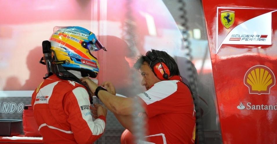 19.abr.2013 - Membro da Ferrari ajuda Fernando Alonso a tirar o capacete no dia de treinos para o GP do Bahrein