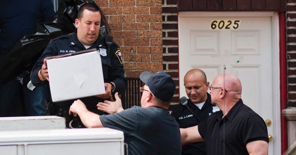 """19.abr.2013 - Policiais retiram caixas com objetos que podem ajudar na investigação do atentado à Maratona de Boston, da casa de Alina Tsarnaeva, em West New York, no Estado de Nova Jersey (Estados Unidos). Tsarnaeva é irmã dos suspeitos de terem executado o atentado a bomba na Maratona de Boston, na última segunda-feira (15). Segundo o FBI, embora """"chocada"""", ela colaborou com as investigações"""