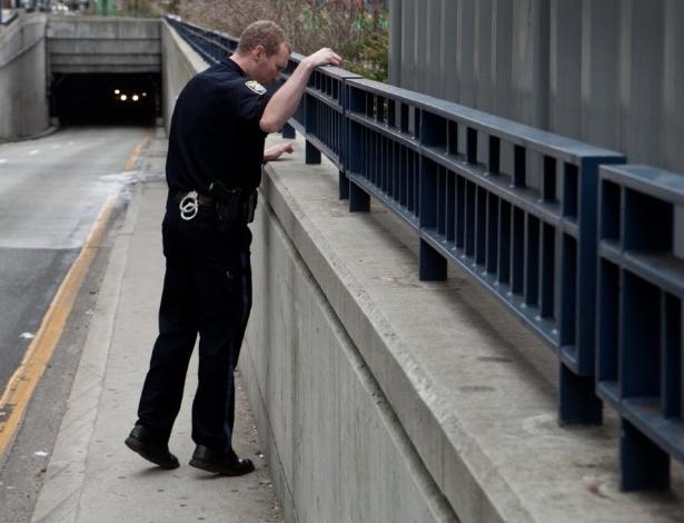 19.abr.2013 - Policial faz busca em Boston por materiais suspeitos depois que cápsulas de bala foram encontradas perto de terminal de ônibus e trens da cidade, nesta sexta-feira (19). A polícia procura por um dos suspeitos dos atentados na Maratona de Boston e pediu aos moradores da cidade que não saiam de suas casas