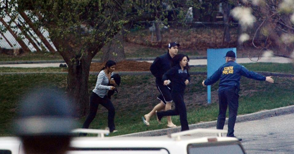 19.abr.2013 - Policial orienta evacuação de uma área onde um dos suspeitos do atentado em Boston estava escondido, em Watertown, cidade próxima a Boston (Estados Unidos). Dzhokhar Tsarnaev, 19, um dos suspeitos, foi preso na noite desta sexta-feira (19), segundo a polícia. Tamerlan Tsarnaev, 26, seu irmão, e também suspeito, morreu durante troca de tiros com a polícia na madrugada desta sexta-feira