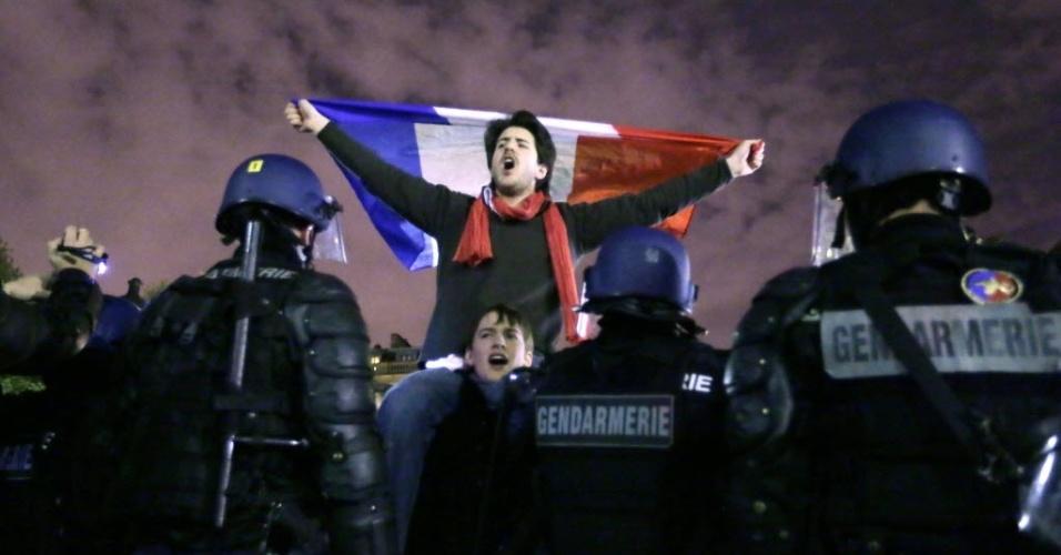 """8.abr.2013 - Apoiador do movimento contrário ao casamento gay """"La Manif Pour Tous"""" segura uma bandeira francesa durante manifestação em Paris, na noite de quinta-feira (18). A tensão aumenta na França ao se aproximar a data da adoção da lei que autoriza o casamento entre pessoas de mesmo sexo, o que levou o presidente François Hollande a denunciar nesta quinta-feira os violentos atos homofóbicos depois dos novos choques registrados em uma manifestação na véspera e uma agressão ocorrida em um bar gay"""