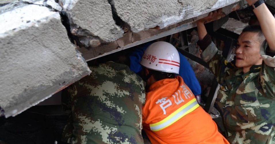20.abr.2013 - Equipe de resgate tenta retirar criança de escombros de residência na cidade de Yaan, no sudoeste da China, neste sábado (20). Mais de cem pessoas morreram por causa de um tremor de magnitude 6,6, que começou às 8h no horário local, no condado de Lushan
