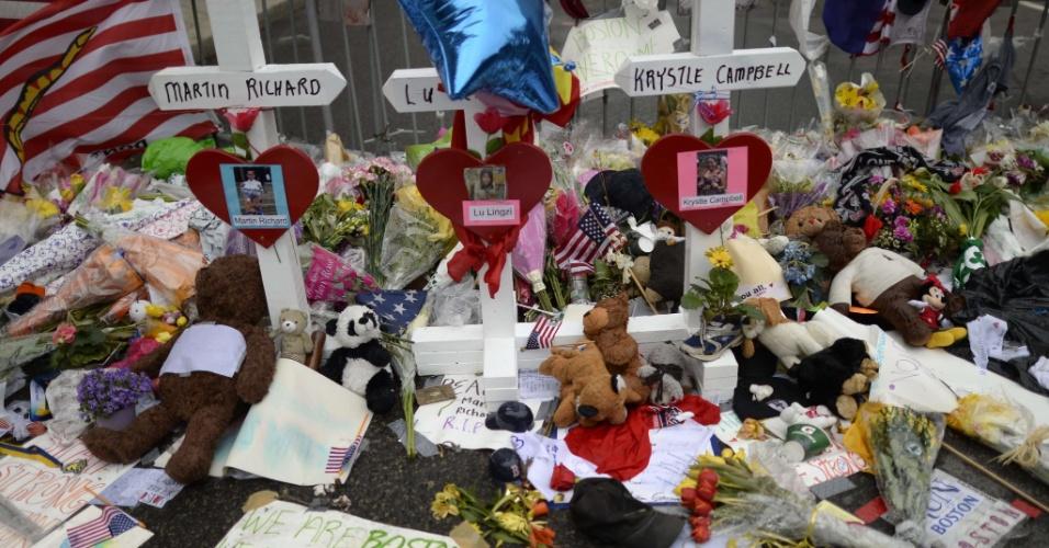 20.abr.2013 - Flores e presentes são deixadas na calçada no local dos atentados que mataram três pessoas, em Boston