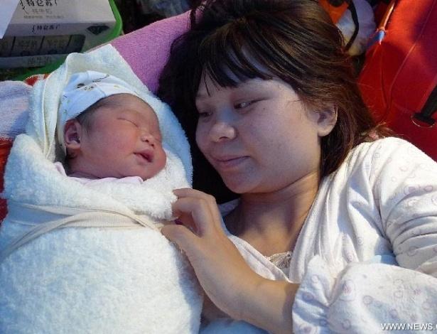 20.abr.2013 - Mãe observa seu bebê recém-nascido na cidade de Yaan, na província chinesa de Sichuan. A criança nasceu em uma ambulância quase duas horas após o terremoto que atingiu a região e deixou centenas de mortos e mais de 3.000 feridos