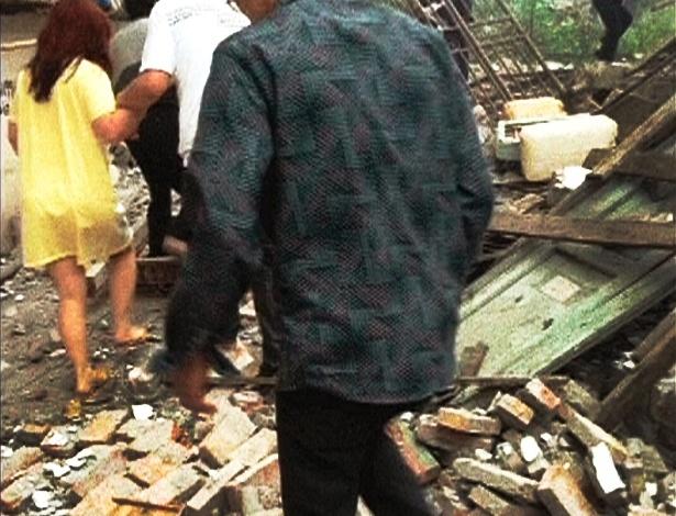 20.abr.2013 - Pessoas caminham em meio a destroços de edifícios atingidos pelo terremoto ocorrido na província chinesa de Sichuan, no sudoeste do país, com intensidade 6,6. O tremor, ocorrido em região próxima à do terremoto de 2008, que matou quase 70 mil pessoas, deixou mais de cem de mortos e milhares de feridos