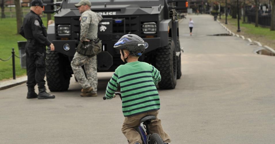 30.abr.2013 - Garoto anda de bicicleta próximo a uma viatura da polícia norte-americana, próximo ao local onde um dos suspeitos de ter cometido os atentados em Boston foi encontrado