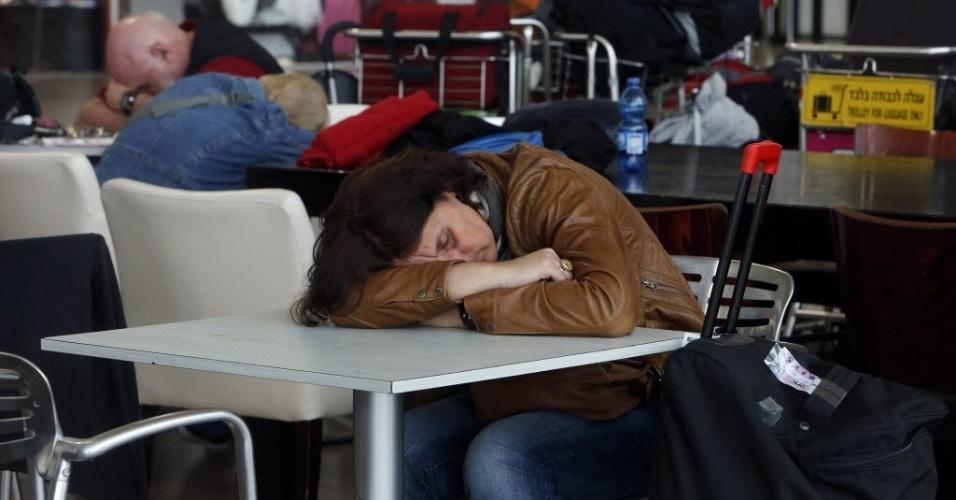 21.abr.2013 -Passageiros dormem na sala de embarque do aeroporto internacional de Tel-Aviv (Israel). Uma greve dos funcionários das três principais companhias aéreas do país paralisou os voos estrangeiros das empresas neste domingo (21). Os trabalhadores protestam contra os planos do governo israelense de eliminar barreiras para empresas aéreas de toda a Europa operarem no país