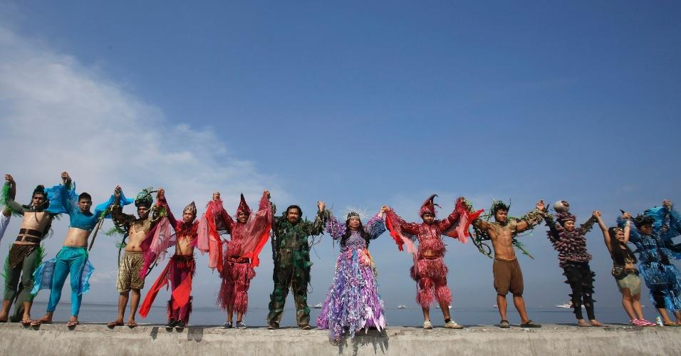 """21.abr.2013 - Ambientalistas e artistas do Centro Cultural das Filipinas vestindo trajes típicos dão as mãos durante o """"Salve a Baía de Manila"""", evento para celebrar o Dia da Terra"""
