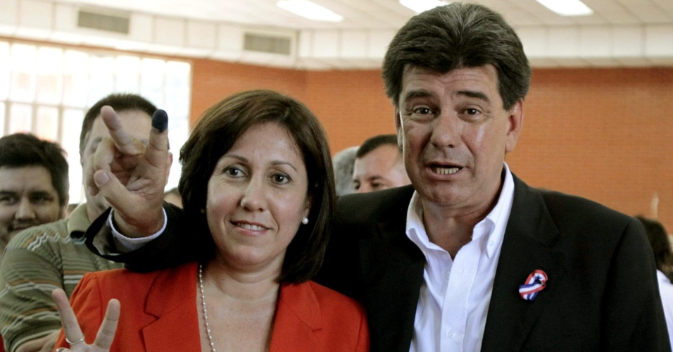 """21.abr.2013 - Candidato do partido Liberal, Efraín Alegre faz o """"V da """"vitória"""" junto com a esposa, Mirian. Mais de três milhões de paraguaios vão às urnas neste domingo (21) nas sextas eleições realizadas desde a redemocratização no país, em 1989"""