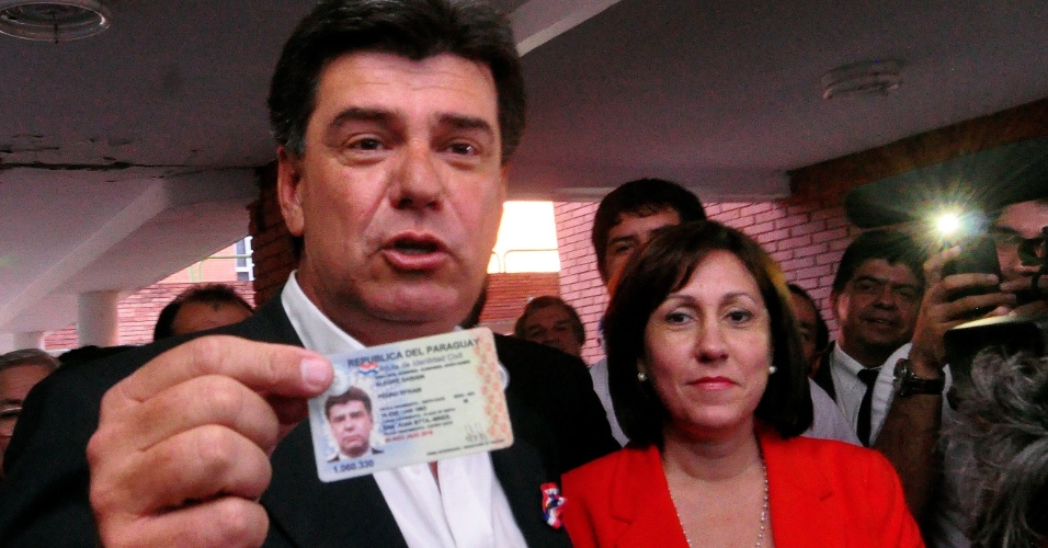 21.abr.2013 - Candidato do partido Liberal, Efraín Alegre, mostra sua carteira de identidade antes de votar, junto com a esposa, Mirian. Mais de três milhões de paraguaios vão às urnas neste domingo (21) nas sextas eleições realizadas desde a redemocratização no país, em 1989