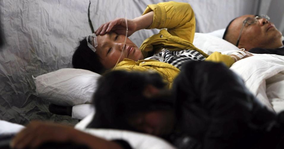 21.abr.2013 - Chinesa ferida recebe tratamento em hospital improvisado na cidade de Yaan, no sudoeste da China, que foi atingida pelo terremoto de magnitude 6,6 na escala Richter que abalou o país neste sábado (20). Equipes de resgate ainda tentam encontrar sobreviventes, mas enfrentam dificuldades para trabalhar em áreas remotas, que ficaram isoladas por causa de deslizamentos de terra