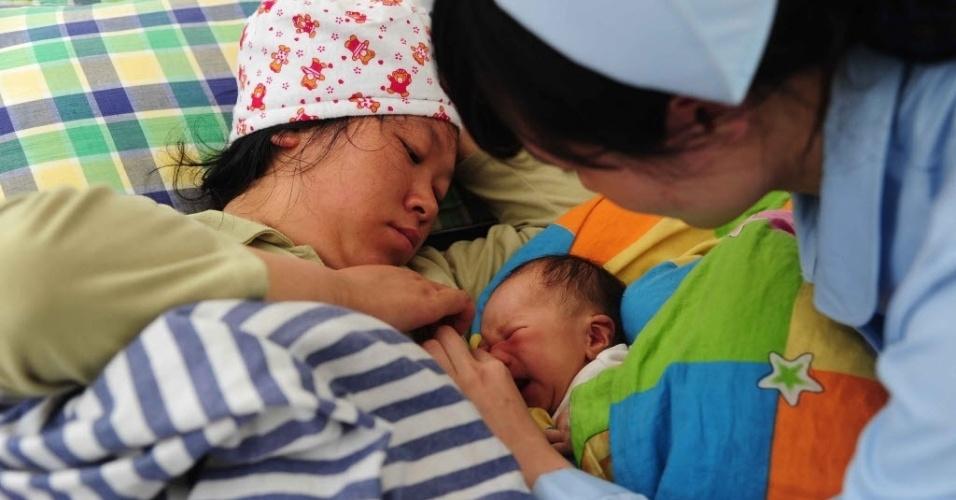 21.abr.2013 - Enfermeira chinesa cuida de mulher e recém-nascido, em meio ao resgate de vítimas do forte terremoto que atingiu Sichuan (China)