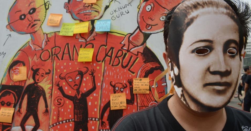 21.abr.2013 - Homem veste máscara de Raden Ajeng Kartini, considerada uma heroína na Indonésia, durante manifestação contra abusos sexuais em mulheres